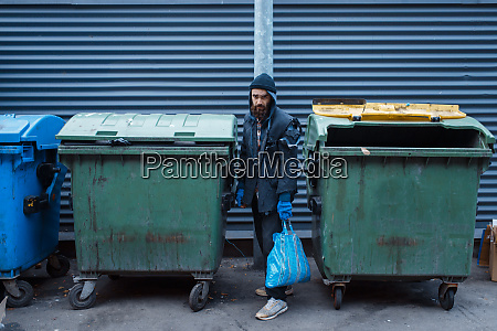 bearded bum searching food in trashcan
