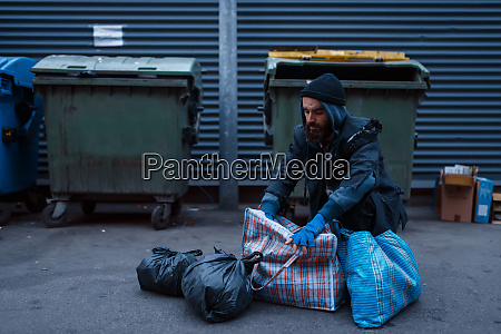 bearded dirty poor at the trashcan