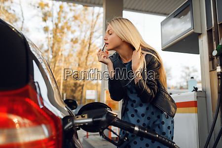 woman fuels vehicle on gas station