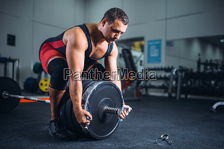 male powerlifter prepares a barbell in