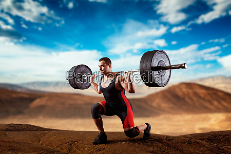 muscular weightlifter doing squats with a