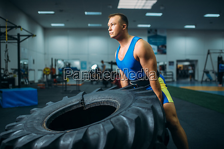 athlete doing exercise with truck tyre
