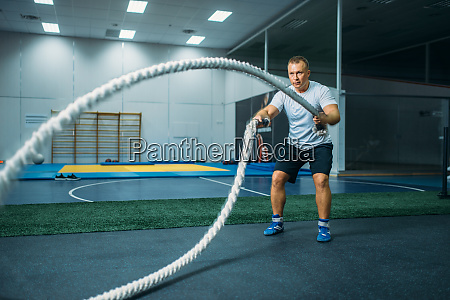 male athlete with ropes in gym