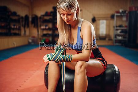 female kickboxer sitting on punching bag