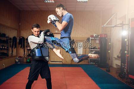 male kickboxer doing kick in jump