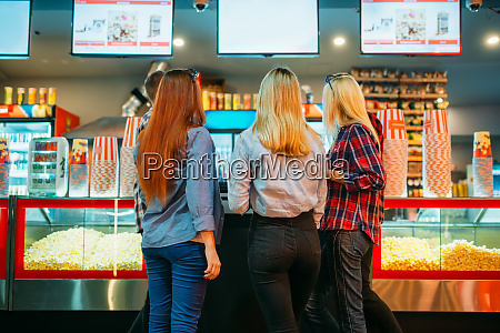 friends choosing food in cinema bar
