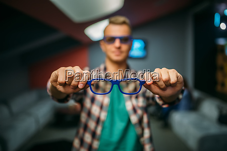 male spectator shows 3d glasses in