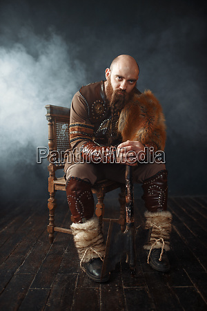 bearded viking with axe sitting on