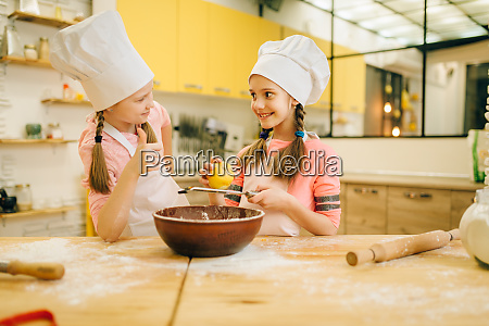 little girls cooks in caps sniffing