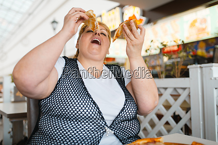fatty woman eating pizza unhealthy food