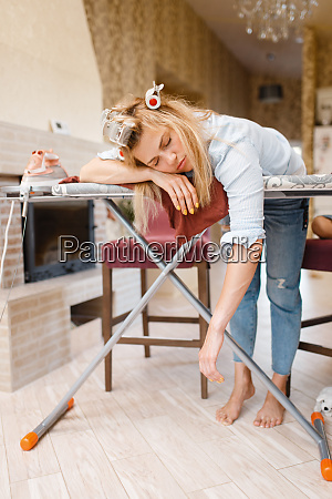 tired housewife slepping on the ironing