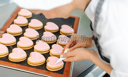 confectioner woman writing messages on cookies