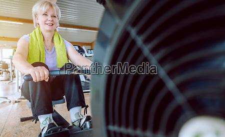senior woman on the rowing machine