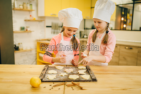 two little girls cooks spread out