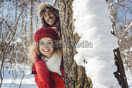 playful couple in the snow hiding