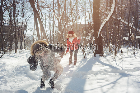 woman throwing snowball on her guy