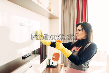 housemaid cleans furniture with a cleaning