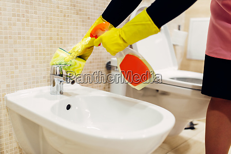 maid cleans the bidet with a