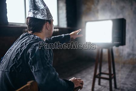 man in aluminum foil helmet reaches