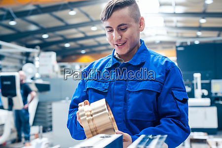 apprentice in metalworking looking at workpiece