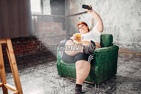 overweight woman drinks beer laziness and