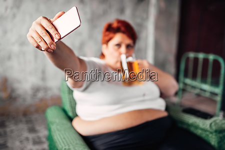 overweight woman drinks beer and makes