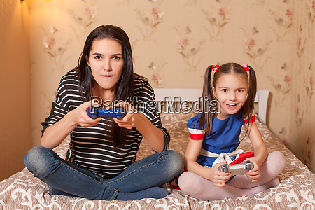 mother and daughter plays game console