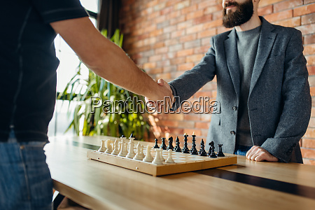 chess players shake hands before the