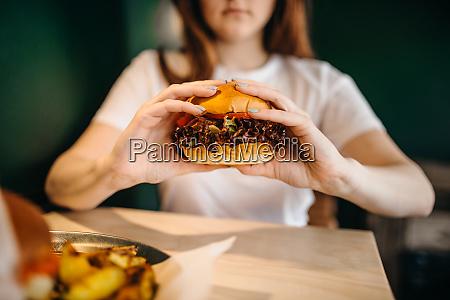 female person eats fresh burger