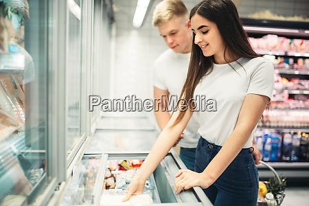young couple choosing frozen goods in