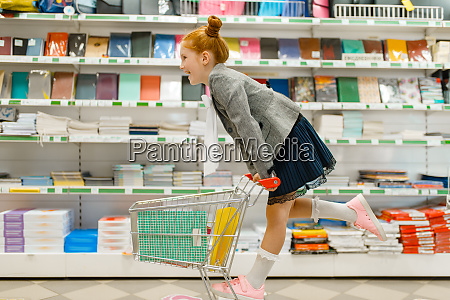 schoolgirl with cart shopping in stationery