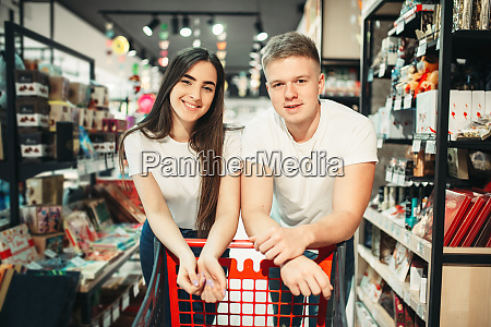 young couple with cart confectionery department