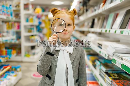 schoolgirl choosing magnifying glass stationery