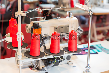 spools of red threads on sewing
