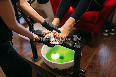 pedicure master in gloves doing cosmetic