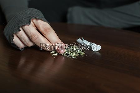 addict hands making marijuana jamb closeup