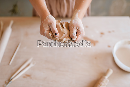 female master shaping clay pottery workshop