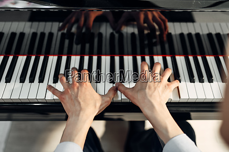 male pianist hands on grand piano