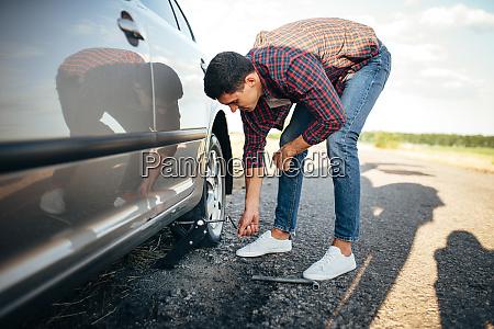 man jack up broken car wheel