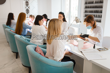 group of girlfriends manicure in beauty