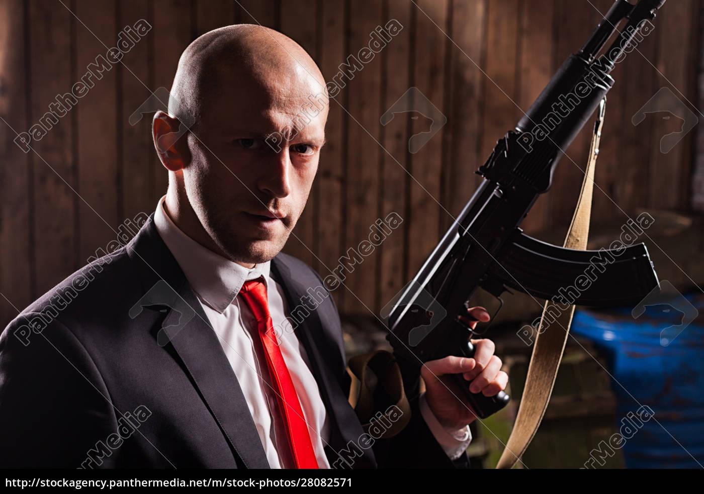 contract, killer, holding, machine, gun, in - 28082571