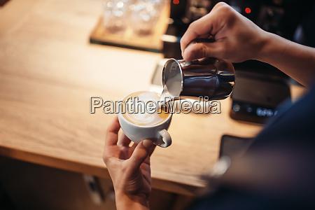 barista hand pours cream into the