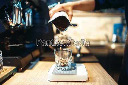 barista hand pours coffee beans into
