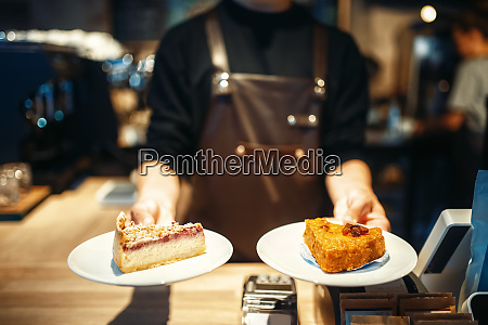 barista holding in hands plates with
