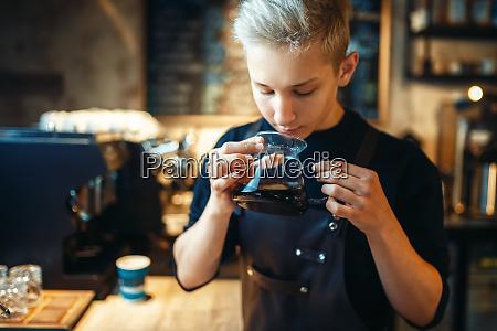 male barista sniffs fresh prepared black