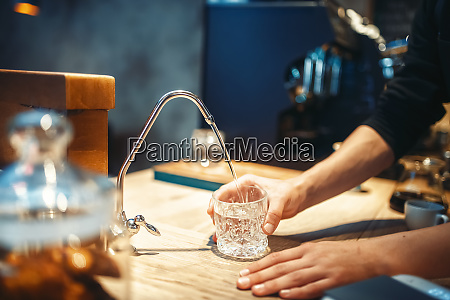 male barista pours filtered water into