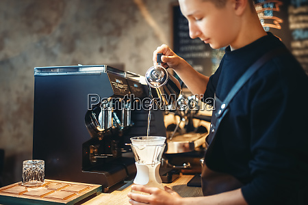 barista pours hot water into the