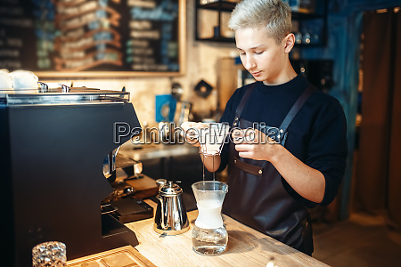 young male barista makes coffee at