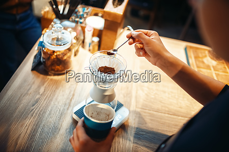 male barista pours ground coffee into