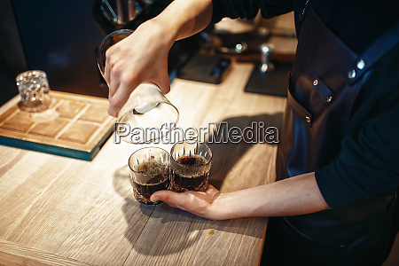 young male barista makes fresh black